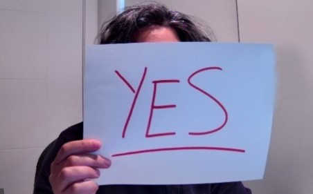 woman holding a paper sign with yes written